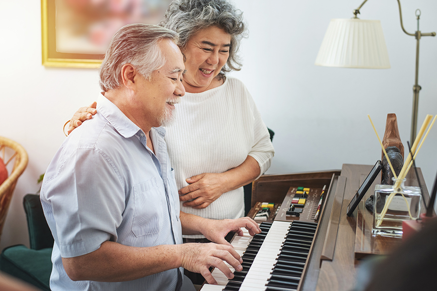 Senior gentleman practices piano in retirement home while woman listens