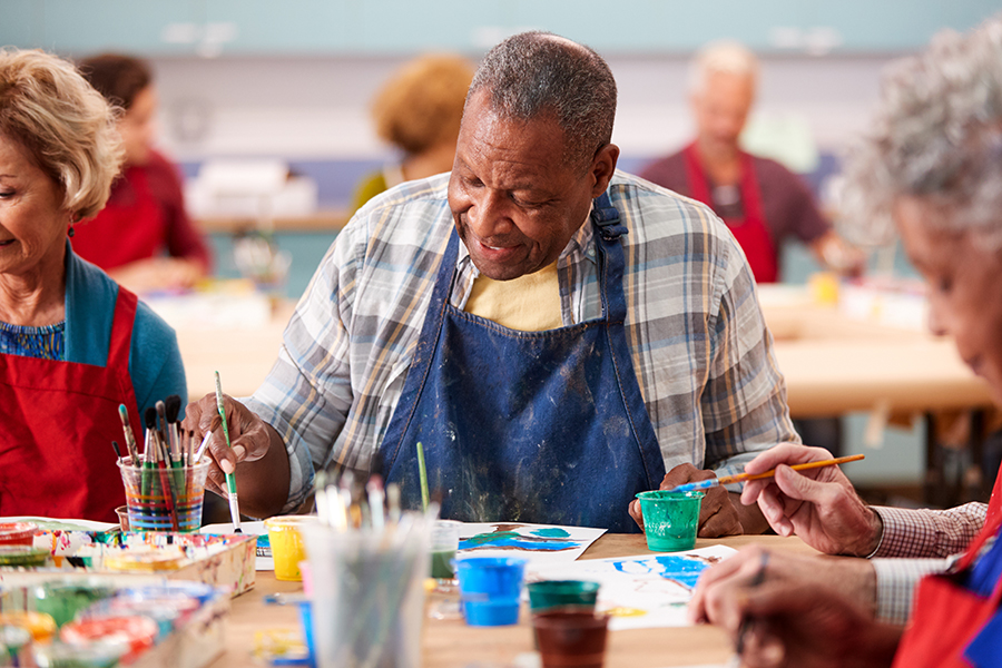 Senior man painting with brush during art class at community centre