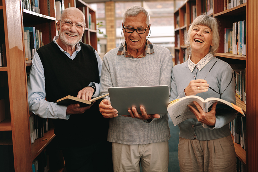 Three happy seniors holding books in the library